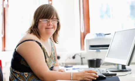 Disab: Portrait of a woman with down syndrome using computer at office