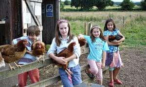 Children holding hens on a farm
