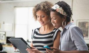 Women using digital tablet in office