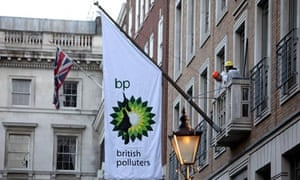 Greenpeace activists hoist a flag after climbing onto a balcony at BP headquarters in London