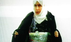 A video grab image shows Sajida al-Rishawi confessing on Jordanian TV to trying to detonate a suicide bomb, showing how she strapped a device to her body.
