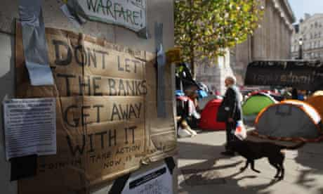 A man walks by protest posters at the Occupy London camp outside St Paul's Cathedral