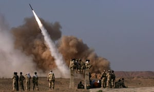 Iranian revolutionary guards personnel watch the launch of a Zelzal missile in June