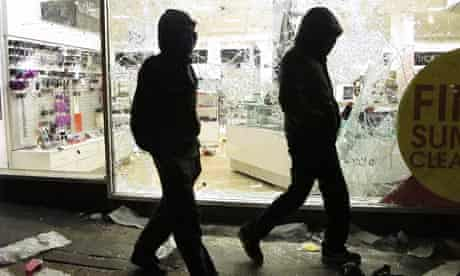 Riots: Hooded youths walk past a looted Debenhams store in Clapham Junction