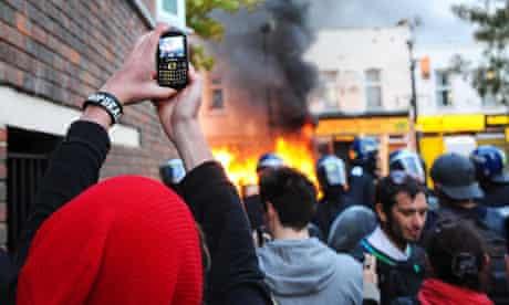 Riots: Spectators film a burning car in Hackney