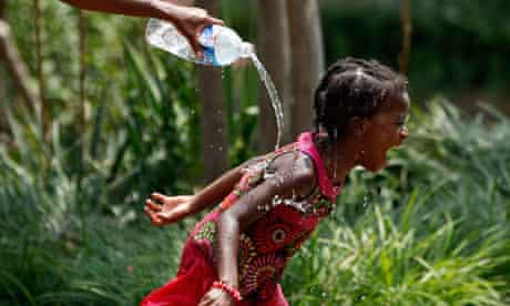 A mother squirts water to cool off her daughter and beat the heat in Washington