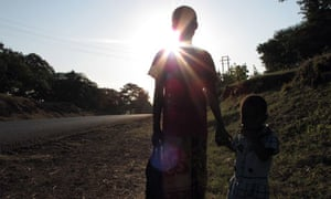 An eleven-year-old girl walks along a road with her sister in Tanzania