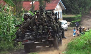 Democratic Republic of the Congo government soldiers ride on the back of a truck, in Minova