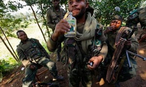 A Democratic Republic of the Congo government soldier takes a sip of home-made whisky