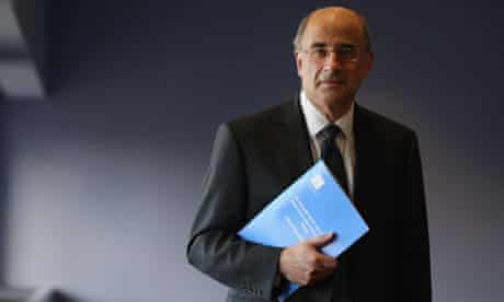 Lord Justice Leveson poses with a summary report into press standards