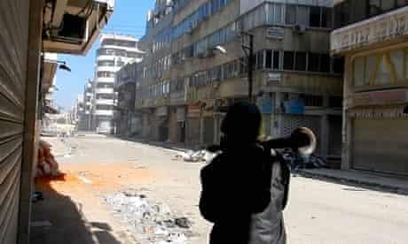 A man carries a rocket propelled grenade in the al-Hamidiya neighbourhood of Homs, Syria