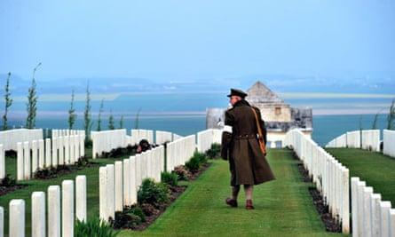 An Australian wearing a First World War uniform walks past graves on Anzac Day