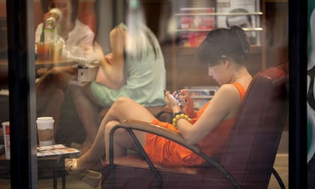 A woman looks at a smartphone as she sits in a cafe in Beijing, China