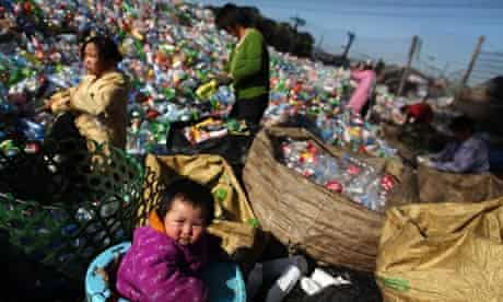 People sort out empty plastic bottles in a recycling centre in Changping district in Beijing, China