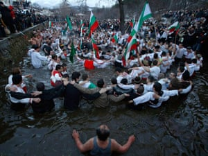 Men dance in the icy waters of the Tundzha
