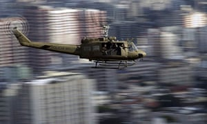 A Brazilian military police helicopter flies over the Lins favela in Rio de Janeiro, during peace op