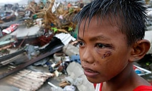 A boy who was wounded by flying debris in Typhoon Haiyan stands at the ruins of his family's house i