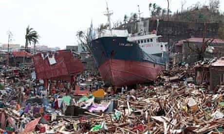 Super typhoon Haiyan: survivors walk past a ship that lies on top of damaged homes