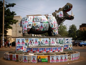 A statue of a hippopotamus is covered with election posters at a roundabout. Mali is holding parliam