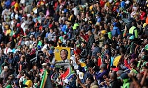 A man holds a placard with an image of Nelson Mandela at the FNB Stadium in Johannesburg