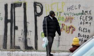 A pedestrian walks by graffiti in downtown Detroit.