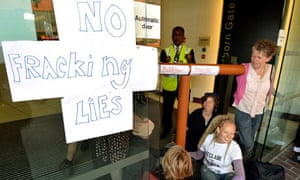 Anti-fracking demonstrators sit with their hands super-glued to each at the offices of Bell Pottinger