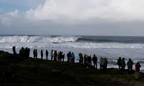 People watch as surfers ride big waves at Mullaghmore