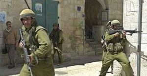 Israeli soldiers take positions on a street corner facing the Church of the Nativity in the West Bank town of Bethlehem