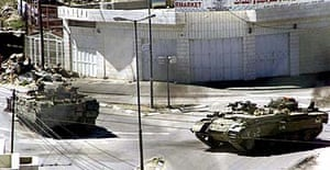 Israeli tanks destroy a Palestinian police position in the West Bank town of Hebron