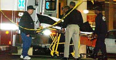 Medical examiners wheel the body of the female shooting victim to an ambulance