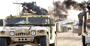 US Humvees pass a recent battlefield
