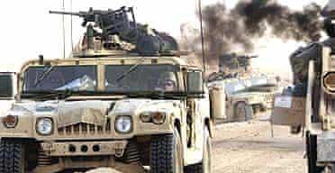 US Humvees pass a recent battlefield