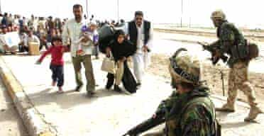 Iraqi civilians approach a checkpoint in Basra