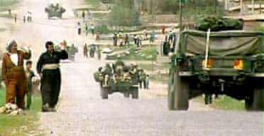 Two civilians wave to US soldiers near Kalak, on the northern front of the war in Iraq