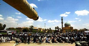 Shia demonstrators pray in front of a US army tank guarding the Sheraton and Palestine hotels in central Baghdad