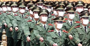 Chinese military police wear masks to protect against the Sars virus as they march in front of Beijing's Tiananmen Gate