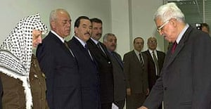 Palestinian leader Yasser Arafat (left) watches as Mahmoud Abbas ia sworn in as Palestinian prime minister