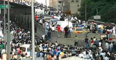 Pedestrians stream on to New York's 59th St Bridge to Queens after a power cut crippled the city