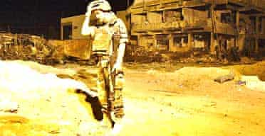 An Italian soldier next to the barracks in Nassiriya destroyed by a suicide bomb attack yesterday. At least 18 Italians and eight Iraqis were killed