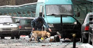 A police officer works with a sniffer dog at the site of an explosion outside the National hotel in central Moscow