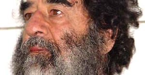 A photo of Saddam Hussein after his capture is shown during a press conference in Baghdad