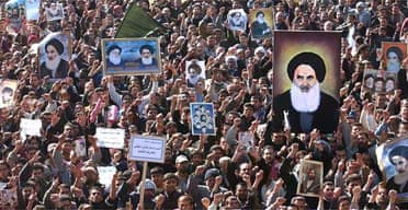 Tens of thousands of Shia Muslims march in Baghdad carrying portraits of Grand Ayatollah Ali al-Husseini al-Sistani and other Shia clerics to demand an elected government. Photograph: Muhammed Muheisen/AP