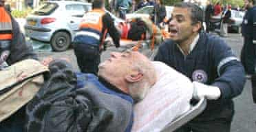 A wounded Israeli man is evacuated from the site of a suicide bombing in Jerusalem that killed at least 10 people