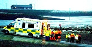 Rescue workers carry bodies into an ambulance at Morecambe lifeboat station after a group of Chinese cockle pickers were trapped by the rising tide