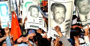 Opposition supporters hold posters of Pakistani nuclear scientist Abdul Qadeer Khan at a rally in Karachi