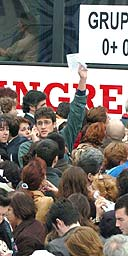 People crowd around a bus to donate blood in Madrid