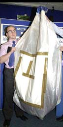 Metropolitan police detectives at New Scotland Yard display a bag similar to the one in which half a ton of ammonium nitrate fertiliser used in the manufacture of explosives was discovered at an address in Hanwell, west London