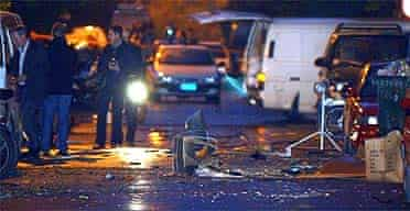 Police investigators search the area behind a police station in Athens after three bombs exploded