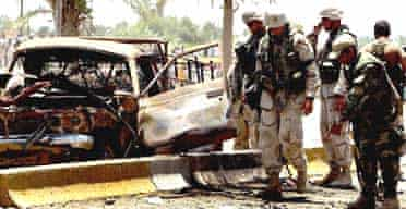 US army soldiers and Iraqi Civil Defense Corps investigate near the bombed out remains of a truck