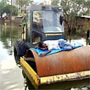 A construction worker takes a nap on a roller after floods inundated much of Dhaka, Bangladesh